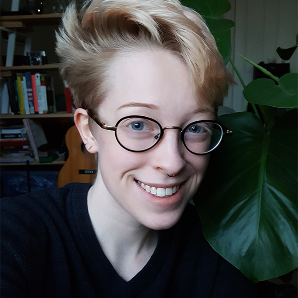 A photo of me. I'm caucasian and have very short blond hair that shwooshes up like a tidal wave. I have a nice smile and almost circular glasses. I'm wearing a black v-neck sweater and am sitting next to a very large plant that I think of as my friend. In the background you can see some books on a shelf and my guitar.